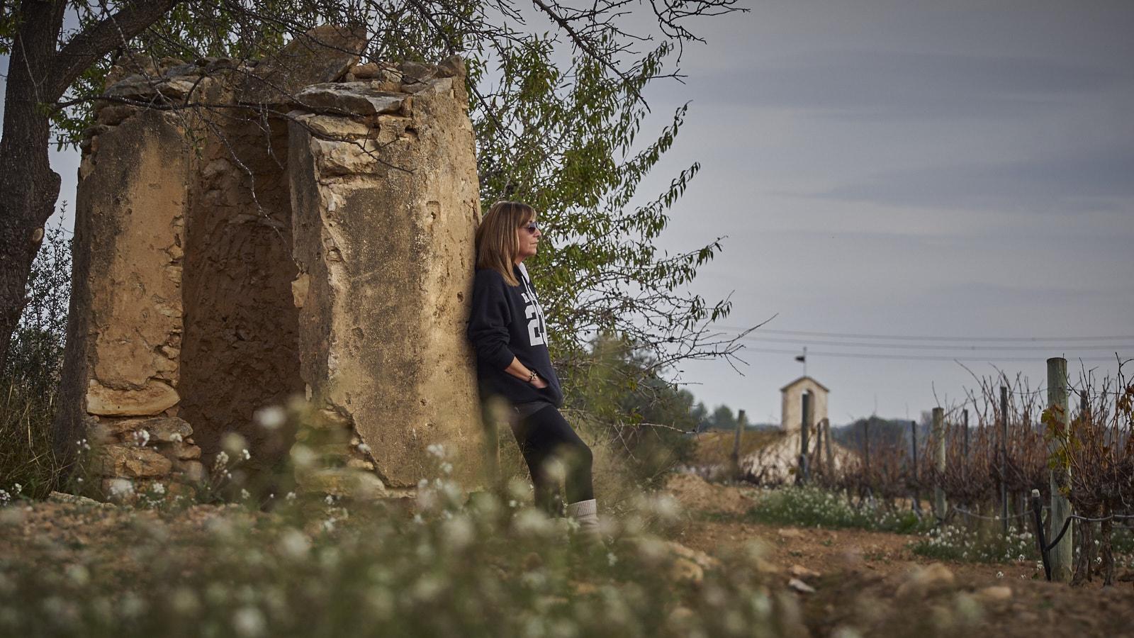 Model entre vinyes amb fons d'una ermita